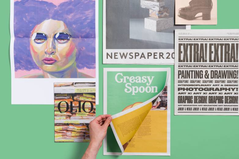 A green background with newspapers laid out and one hand opening the first page of one.